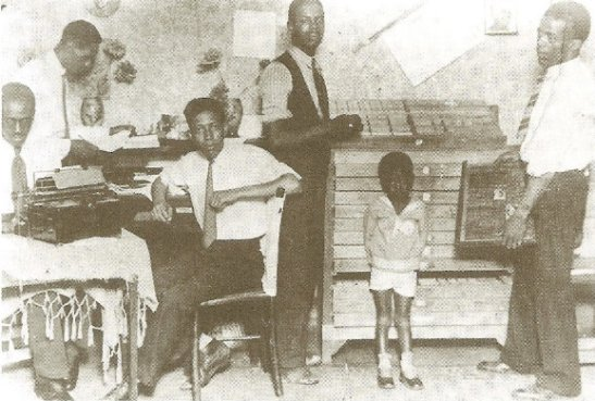 "Átila de Morais, Manoel Antônio dos Santos, Luís Braga, Henrique Cunha, Raul (José Correia Leite's son) and Gentil de Castro; at work on the ""O Clarim d'Alvorada"" newspaper"