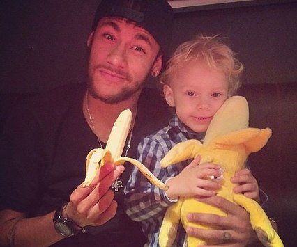 "Neymar, pictured with his son, kick off the ""We're all monkeys"" campaign posing with a banana"