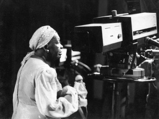 Artista cantando durantes apresentação de programa musical televisivo. Em 2011, completa-se 25 anos de morte de Clementina de Jesus