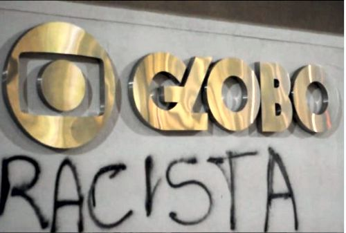 "Protesters wrote the the term ""racista"" (racist) on the front of a Globo TV building"