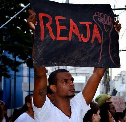 "Protester holds sign of the ""Reaja ou será mort@"" (react or you will be killed) campaign"