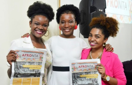 Etiene (center) with Zaika and Énia Dára hold copies of Afronta newspaper