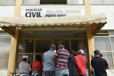 Family members and onlookers wait outside the Civil Police precinct in Ponte Nova, Minas Gerais