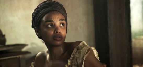 Lucy Ramos em cena como Malena, escrava que chantageia sua patroa, Branca