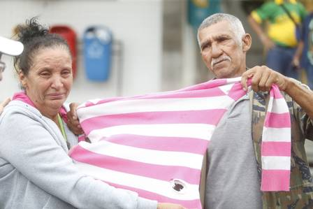 Os pais de Maria Eduarda mostram a camisa que a estudante vestia quando foi baleada (Foto - Antonio Scorza)